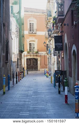 TARRAGONA, SPAIN - JULY 13, 2016: Tarragona (Catalunya Spain): old street in the gothic quarter near the medieval cathedral with painted poles in a row