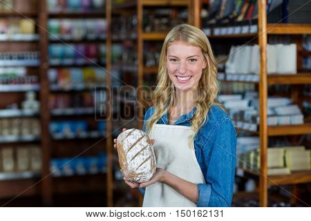 Portrait of smiling female staff holding bread in super market