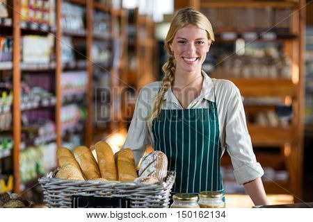 Portrait of happy female staff standing at bread counter in supermarket