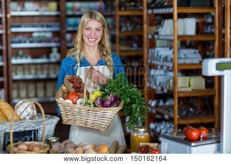 Portrait of smiling female staff holding basket of vegetables in organic section of supermarket