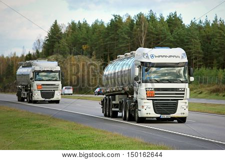 PAIMIO, FINLAND - SEPTEMBER 30, 2016: Two white DAF XF semi tank trucks on freeway in convoy. The ADR code 33-1090 signifies Acetone.