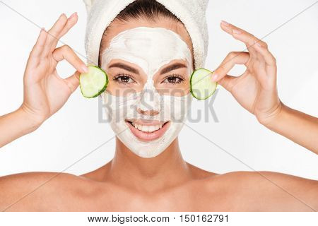 Beautiful woman applying cucumber on her face with cosmetic mask isolated on white background