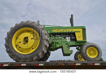 ROSHOLT, SOUTH DAKOTA, August 21, 2015: A John Deere Diesel 720 restored tractor rests on a flat bed trailer at the annual Rosholt Area Threshing Bee held the third full weekend of August.