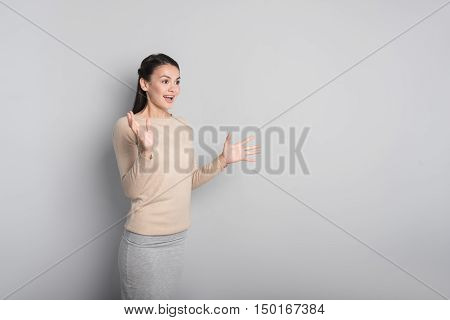 Overwhelmed with emotions. Cheerful surprised young woman expressing wonder and looking aside while standing isolated on grey background