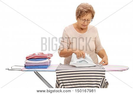 Mature woman ironing clothes on an ironing board isolated on white background