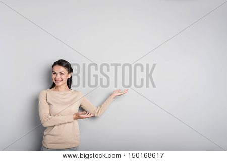 Look here. Pleasant beautiful woman smiling and showing aside while standing isolated on grey background