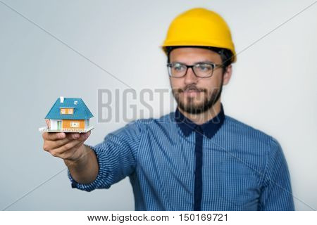 construction engineer showing small house scale model