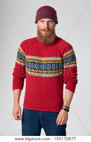 Serious bearded hipster man in woolen sweater and a hat looking at camera, studio portrait over grey background