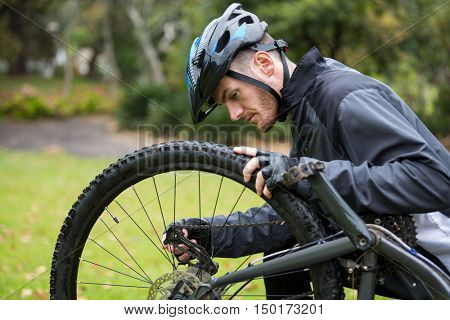 Male cyclist repairing his mountain bike in park