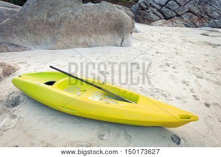 yellow kayak on white sand of tropical beach