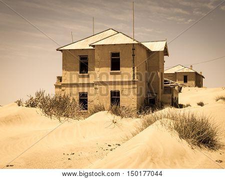 Ghost buildings of old diamond mining town Kolmanskop near Luderitz in Namibia. Abandoned house ruins sunken in the sand dunes of Namib Desert. Vintage toning photography.