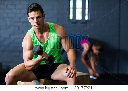 Portrait of serious man lifting dumbbell while sitting in gym