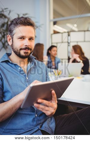 Portrait of smiling businessman using digital tablet against female coworkers in meeting room