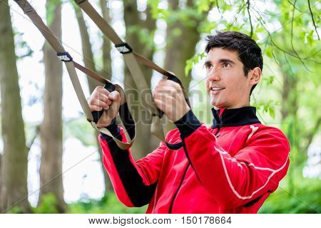 Man at sport training with sling trainer