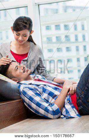 Asian girl caressing her boyfriend lying exhausted on the ground