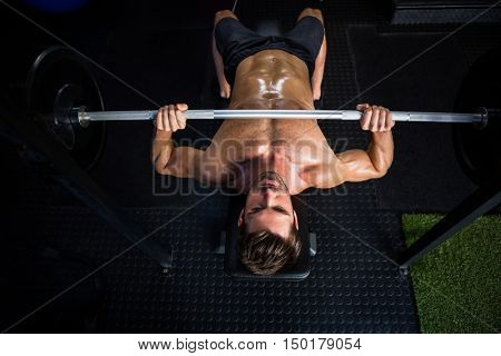 High angle view of shirtless determined man exercising with barbell in gym