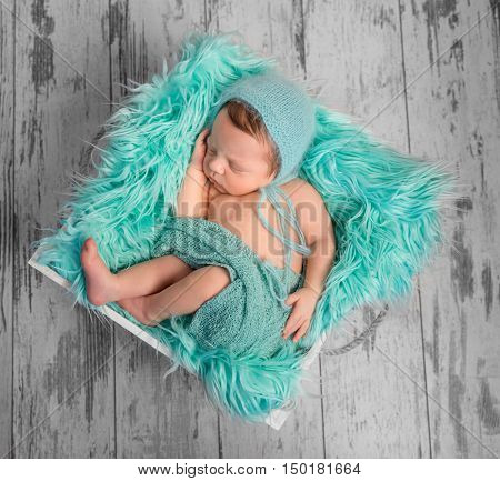 beautiful newborn baby sleeping in hat on square bed with furry turquoise blanket, top view