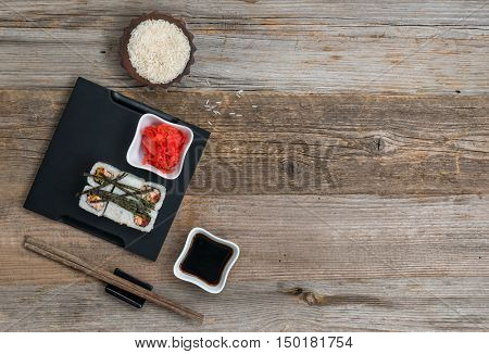 rolls on tray and a bowl of rice on wooden table with text space top view