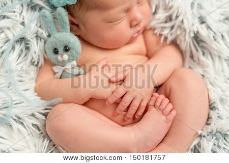funny sleepy newborn baby holding little grey toy, closeup, top view