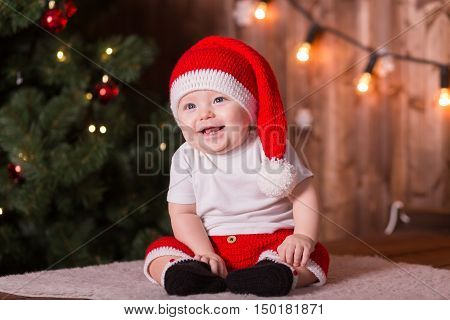 Beautiful little baby with red santa suit and hat celebrates Christmas. New Year's holidays. Baby boy in a Christmas costume smile and laught