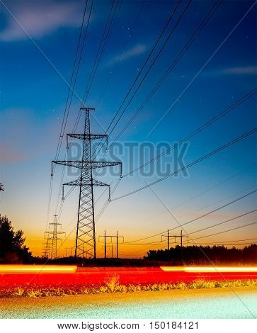 high voltage post. High-voltage tower sky background, besides the highway