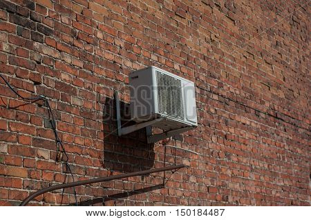 Standard air conditioning on an old red brick wall.
