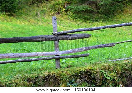 old wooden fence near green meadow border