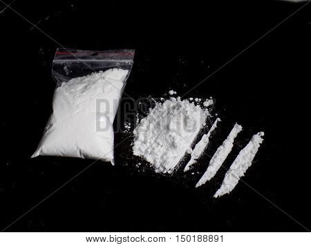 Cocaine drug powder in bag, cocaine pile and lines on black background