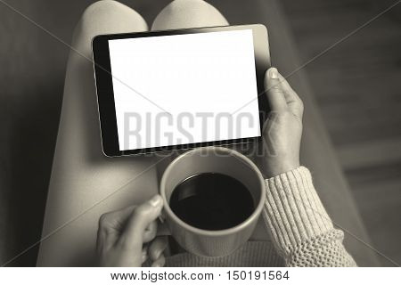 Woman on the sofa with tablet and cup of coffee in hands. Toned photo.
