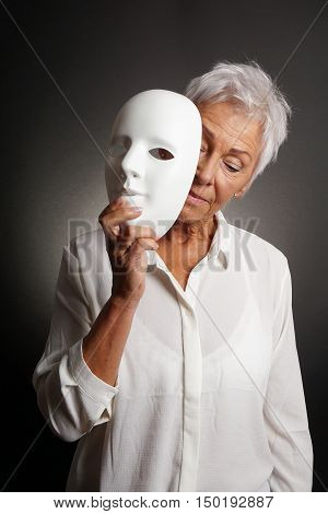 mature woman revaling sad face behind mask. depression concept.