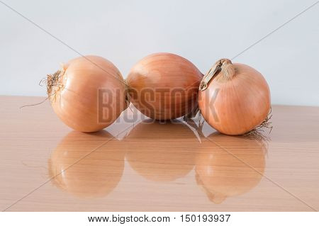 Sliced fresh onion on wooden table reflection