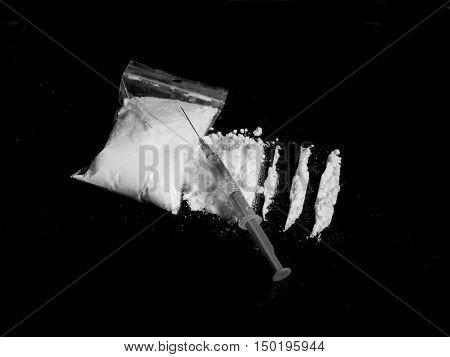 Injection syringe on cocaine drug powder pile and lines and cocaine bag on black background in black and white colors