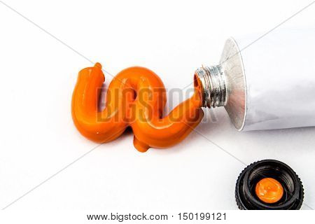 Orange art paint squeezed out of tube onto white background