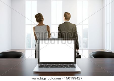Closeup of white laptop placed on wooden desktop in interior with two businesspeople looking out of window with city view. Mock up 3D Rendering