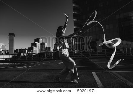 Gymnast girl with ribbon. Professional gymnast woman dancer posing with ribbon on the roof of the building. The skyscraper in the background. Black and white photo.