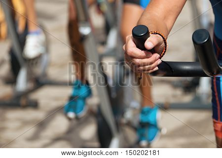 Active people working out on exercise stationary bicycle