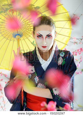 Artistic Portrait Of Japan Geisha Woman With Creative Make-up Near Sakura Tree In Kimono With Umbrel