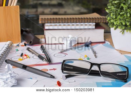 Closeup of messy office desktop with glasses supplies financial reports and other items