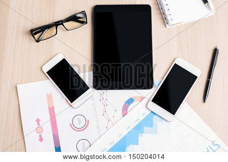 Top view and close up of wooden desktop with blank tablet two cellular phones business report glasses and supplies. Mock up