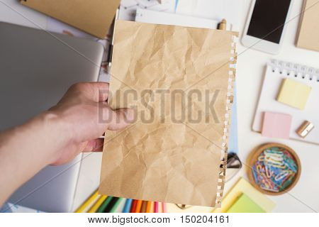 Hand holding brown crumpled paper sheet above messy office desktop with various items. Mock up