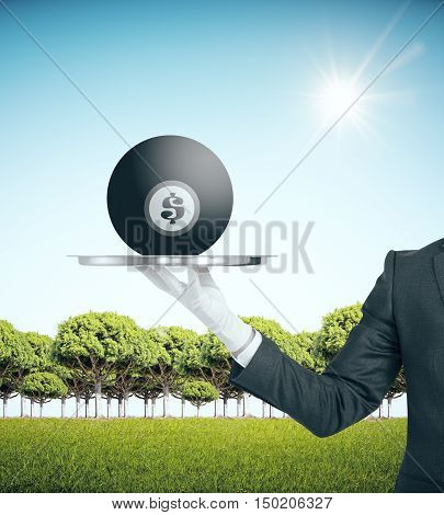 Hand holding bowling ball with dollar sign places on silver tray. Landscape background. Finance and competition concept