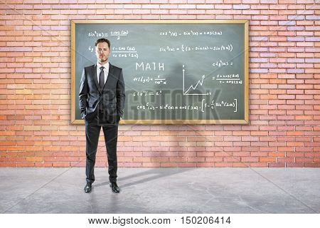 Handsome young businessman in suit standing against chalkboard with mathematical formulas. Education concept
