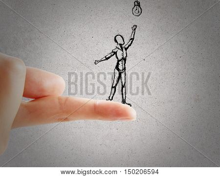 Close up of finger holding abstract sketch of little human trying to reach light bulb on concrete backgroud. Idea concept