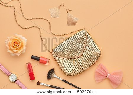 Woman Beauty Accessories Set. Fashion Cosmetic Makeup. Essentials. Fashion Design. Lipstick Brushes, fashion Glamor Gold Clutch Stylish Watches, Rose. Minimal Party Concept. Top view.Cosmetic Overhead