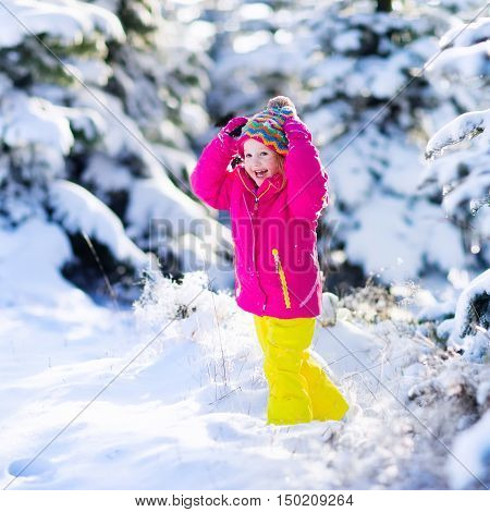 Child running in snowy forest. Toddler kid playing outdoors. Kids play in snow. Christmas vacation in sunny winter park for family with young children. Little girl in colorful jacket and knitted hat.