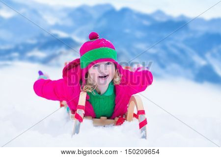 Little girl enjoying a sleigh ride. Child sledding. Toddler kid riding a sledge. Children playing outdoors in snow. Kids sled in the Alps mountains in winter. Outdoor fun for family Christmas vacation