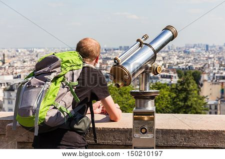 Paris France - July 06 2016: Rear view of man tourist with a backpack looking over Paris landscape from observation deck of the Montmartre with telescope. Montmartre area is popular among tourists in Paris the most visited city worldwide.