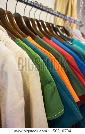 Line of multi colored clothes on wooden hangers in store. Sale
