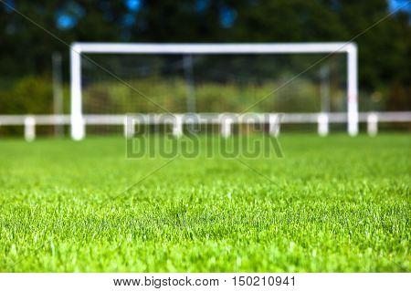 Surface level of grassy field with goal post in background on sunny day
