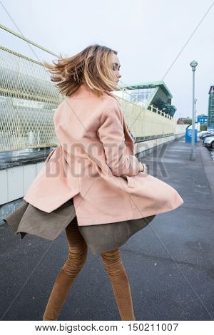 young fashionable woman in coat at windy weather